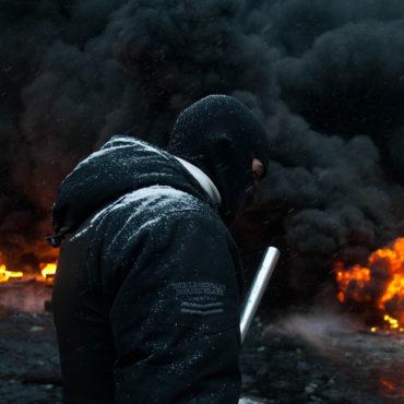 Kiev, Ukraine - 19 January, 2014: unknown radical protest near the burning barricades during the revolution in Ukraine